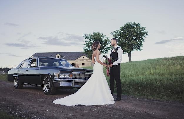 Braut und bräutigam händchen haltend mit einem blumenstrauß