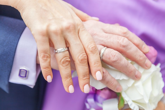 Braut und bräutigam hände mit eheringen vor dem hintergrund des brautstraußes von blumen