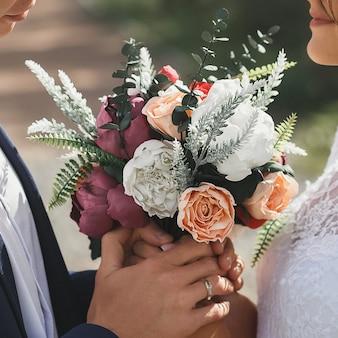 Braut und bräutigam halten brautstrauß mit lila cremigen und weißen rosen im freien