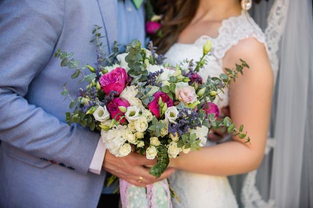 Braut und bräutigam halten bunten hochzeitsstrauß