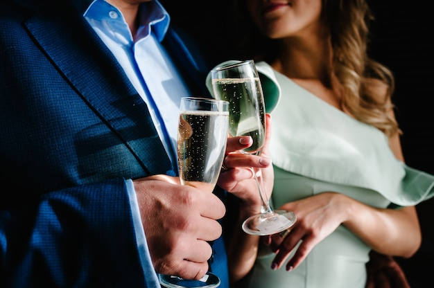 Braut und bräutigam halten ein glas champagner und stehen im raum