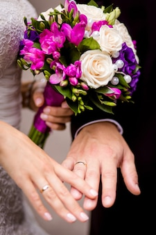 Braut und bräutigam halten händchen mit einem strauß