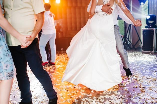 Braut und bräutigam halten händchen und tanzen in der halle. leute tanzen.