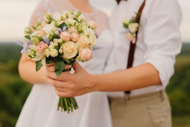 Braut und bräutigam halten hochzeitsstrauß in händen. nahansicht. hochzeitskonzept.