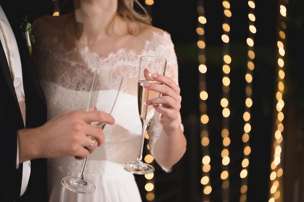 Braut und bräutigam halten kristallgläser mit champagner gefüllt