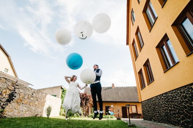 Braut und bräutigam halten luftballons in händen und springen.