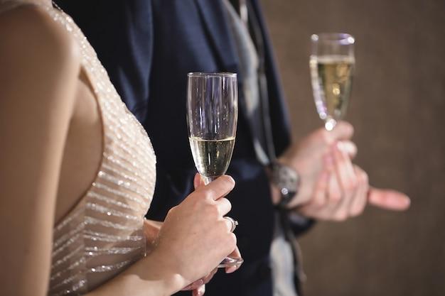 Braut und bräutigam halten mit champagner gefüllte kristallgläser
