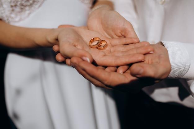 Braut und bräutigam halten noble goldene eheringe in ihren armen