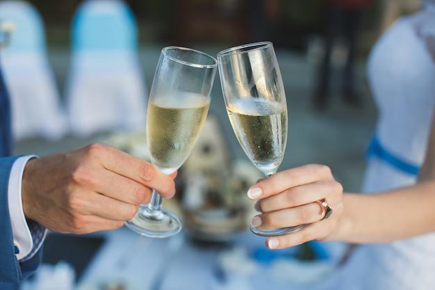 Braut und bräutigam halten schön dekorierte hochzeitsgläser mit champagner