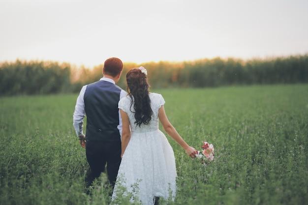 Braut und bräutigam halten sich an den händen und begegnen dem sonnenuntergang. hochzeit