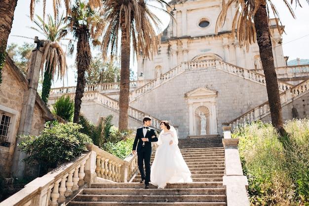 Braut und bräutigam halten sich an den händen und gehen die treppe der kirche der geburt der jungfrau maria in prcanj hinunter
