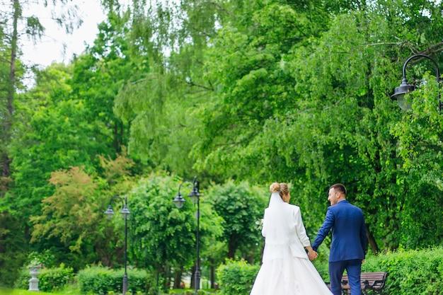 Braut und bräutigam halten sich an den händen und gehen im park spazieren. rückansicht. schwarze laternen auf grünen bäumen