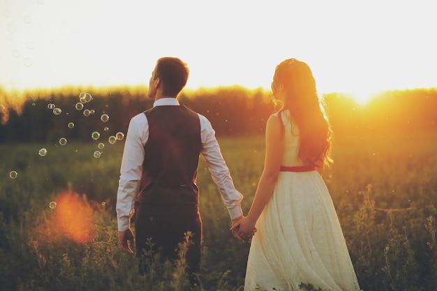 Braut und bräutigam halten sich an den händen und gehen in den park.