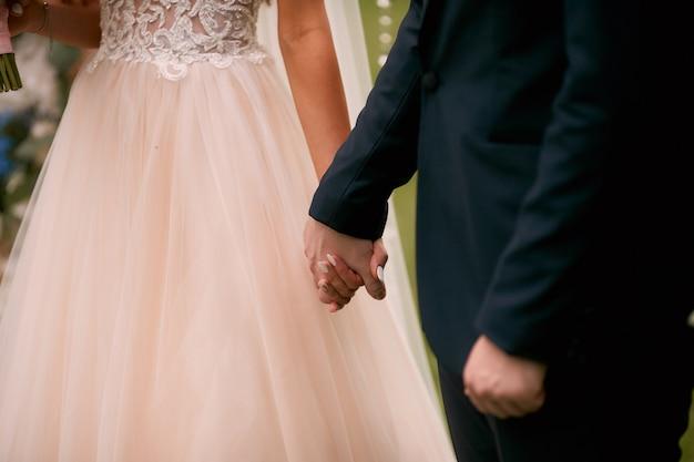 Braut und bräutigam halten sich die hände, die in der kirche stehen