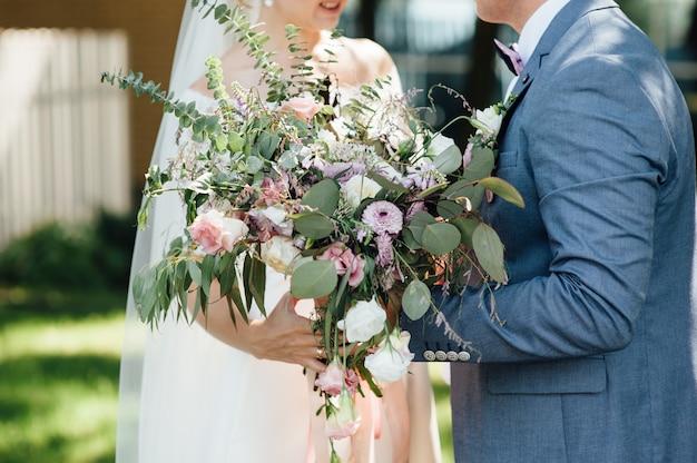 Braut und bräutigam halten zusammen hochzeitsstrauß