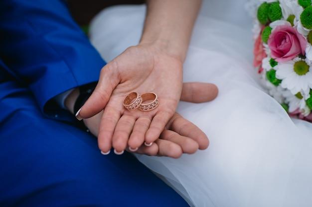 Braut und bräutigam halten zusammen ihre goldenen eheringe