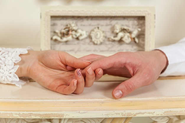 Braut und bräutigam, hochzeit, zwei hände nahaufnahme vor dem hintergrund von engeln.