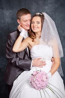 Braut und bräutigam im studio auf grau