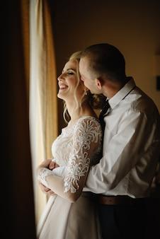 Braut und bräutigam in einem hotelzimmer. der bräutigam umarmt und küsst die braut im nacken
