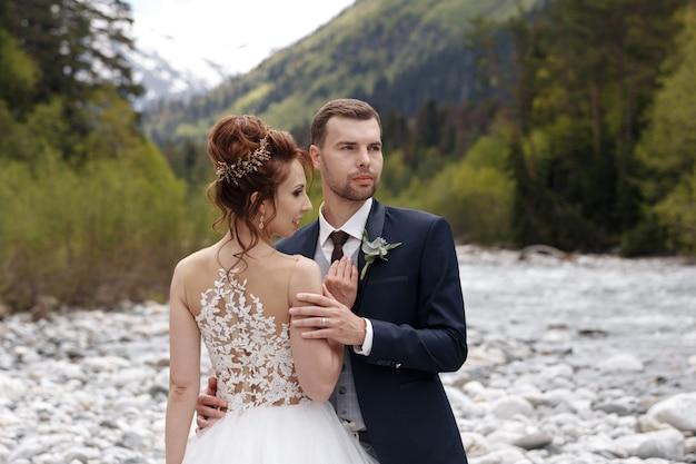 Braut und bräutigam in einem park küssen. paar brautpaar und brautpaar bei einer hochzeit im grünen wald der natur küssen fotoporträt. hochzeitspaar