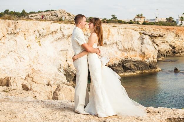 Braut und bräutigam in einem romantischen moment in der natur. stilvolles hochzeitspaar im freien