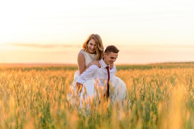 Braut und bräutigam in einem weizenfeld. ein mann trägt einen geliebten auf dem rücken.