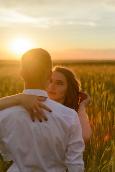 Braut und bräutigam in einem weizenfeld. ein paar umarmt sich während des sonnenuntergangs.