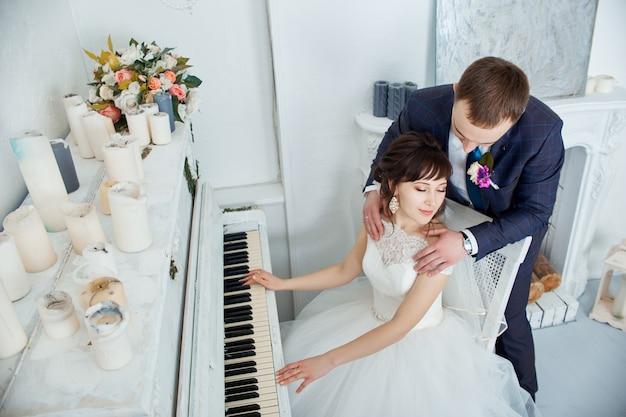 Braut und bräutigam in hochzeitskleidern umarmen sich zu hause. verliebtes paar nach einer hochzeitszeremonie