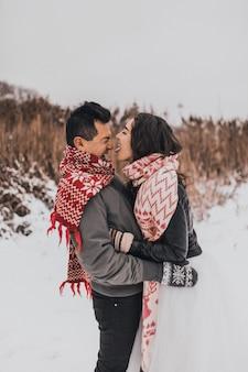 Braut und bräutigam in liebespaar in gestrickten schalhandschuhen im winter und schneeflocken