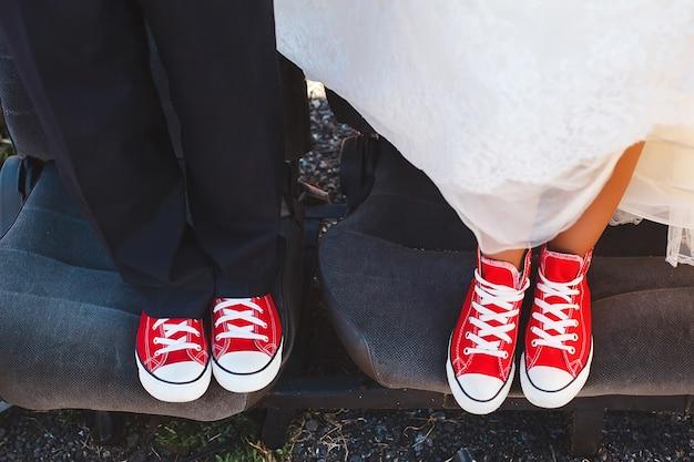 Braut und bräutigam in roten turnschuhen im schrottplatzauto