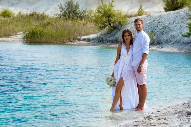 Braut und bräutigam in weißen kleidern mit einem strauß weißer blumen in einem blauen see