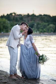 Braut und bräutigam küssen sich bei sonnenuntergang am strand