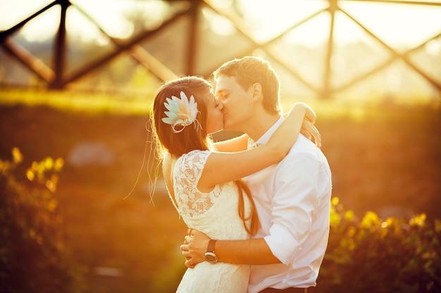 Braut und bräutigam küssen sich im sonnenlicht