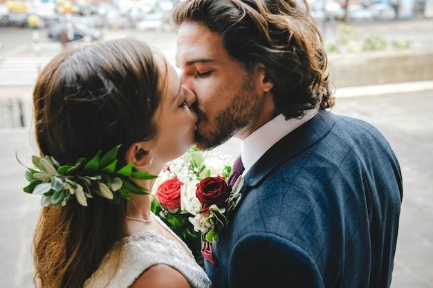 Braut und bräutigam küssen sich vor der kirche