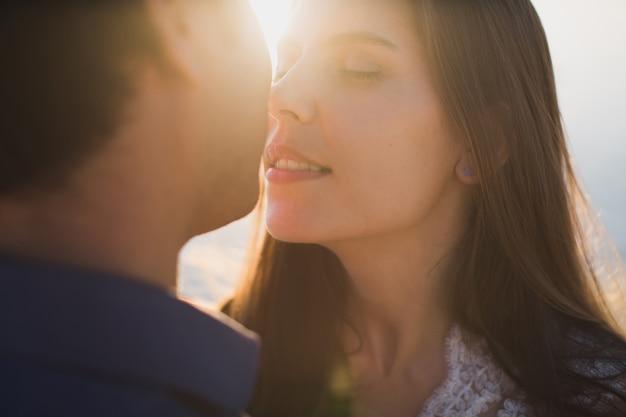 Braut und bräutigam küssen zärtlich. sexy küssen stilvolle paar liebhaber schließen porträt