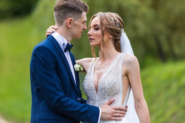 Braut und bräutigam kuscheln während eines hochzeitsspaziergangs, hochzeitstag des schönen paares, schöne outfits des brautpaares.