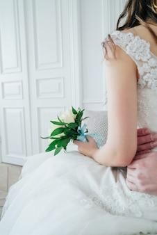 Braut und bräutigam mit blumenstrauß von weißen rosen am hochzeitstag, details nah oben