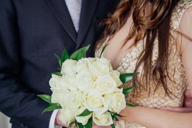 Braut und bräutigam mit blumenstrauß von weißen rosen am hochzeitstag