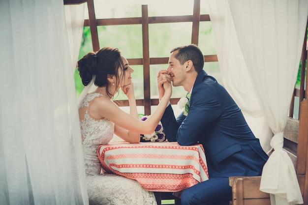 Braut und bräutigam mit dem hochzeitsblumenstrauß, der am tisch in einem café auf der sommerterrasse sitzt