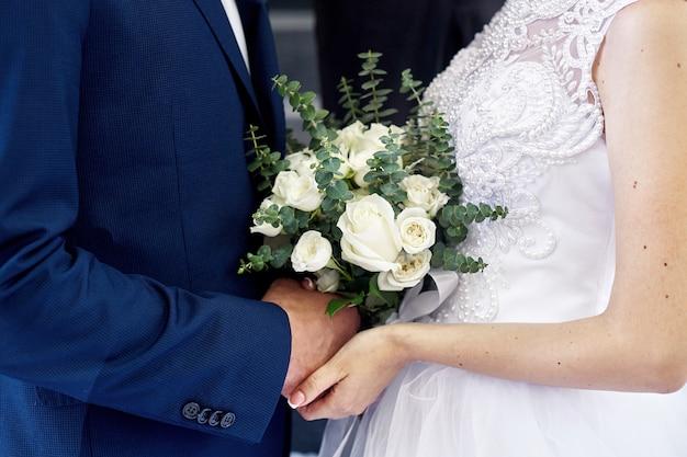 Braut und bräutigam mit einem schönen hochzeitsblumenstrauß bei der zeremonie