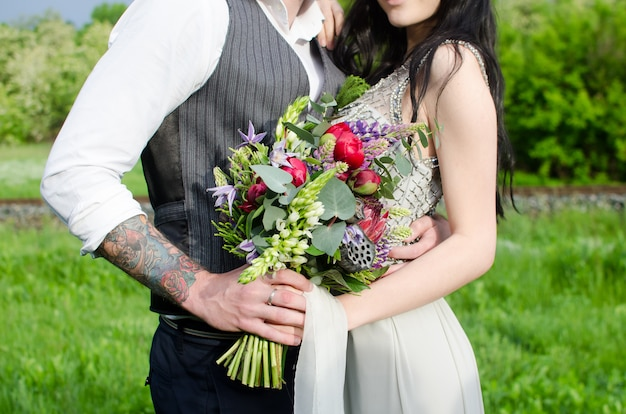 Braut und bräutigam mit hochzeitsblumenstrauß in ihren händen.