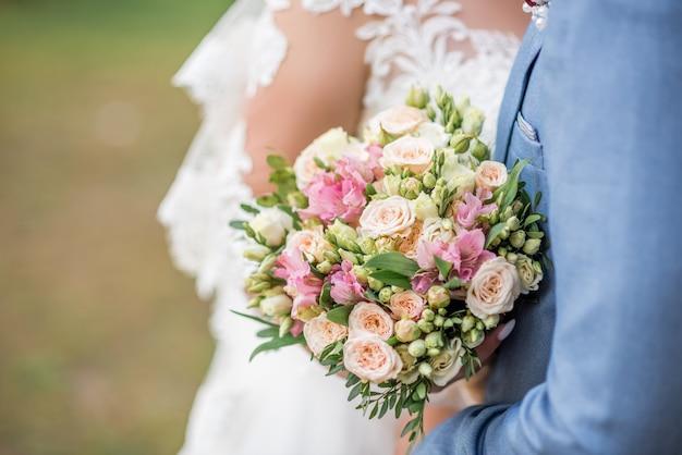 Braut und bräutigam mit hochzeitsblumenstrauß