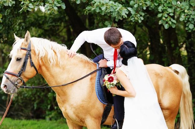 Braut und bräutigam mit pferd. braut und bräutigam auf pferden im wald