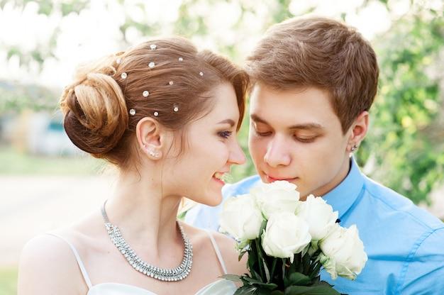 Braut und bräutigam mit weißem brautblumenstrauß von rosen