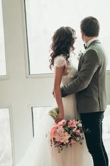 Braut und bräutigam mit wunderschönem hochzeitsstrauß stehen am fenster blick von hinten