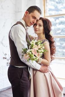 Braut und bräutigam nahe dem großen fenster, das vor der hochzeit umarmt. liebe und zärtlichkeit in jedem look. verliebtes paar, das sich zu hause küsst. ein mann schenkt einer frau einen blumenstrauß
