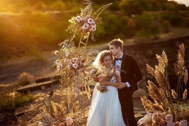 Braut und bräutigam nahe der hochzeitsdekoration bei einer zeremonie auf einer felsenklippe nahe dem wasser bei sonnenuntergang