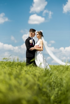 Braut und bräutigam posieren auf der grünen wiese