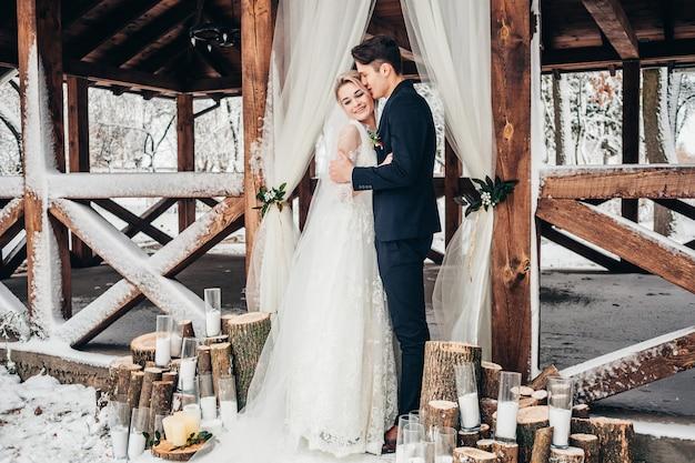 Braut und bräutigam posieren im winter im freien
