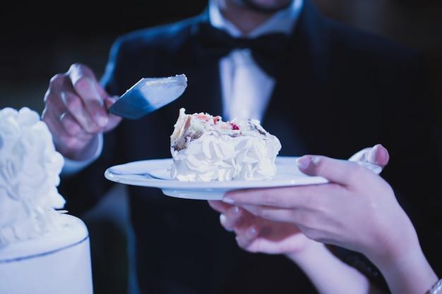 Braut und bräutigam probieren luxuriöse hochzeitstorte, dekoriert mit rosen an der rezeption, catering im restaurant